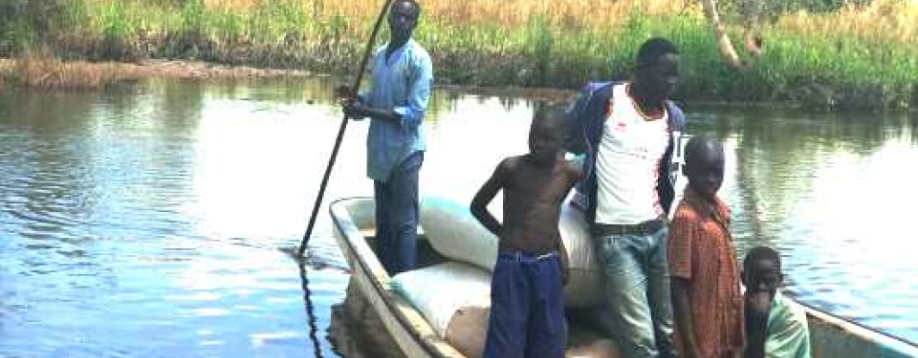 Some people using a boat to link up to Achinga Sub County in Kapelebyong district during rainy season